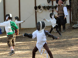A kid happily showing his fencing skills.