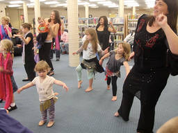 Moms and kids during a ballroom dance lesson.
