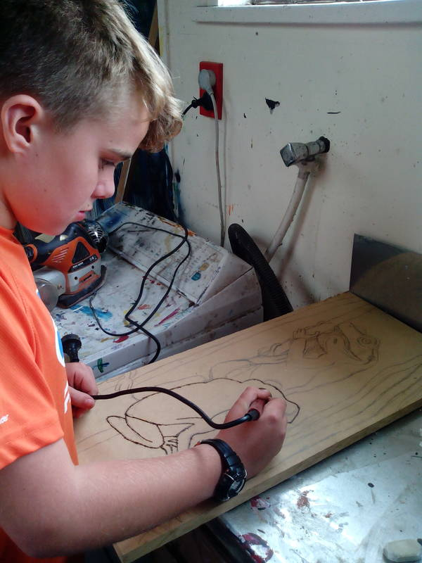 A student doing wood burning after drawing his picture himself